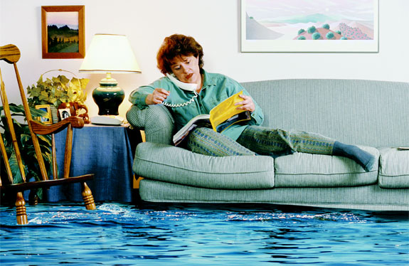 A women sitting on her couch with water all over the floor looking for help by going through her phonebook
